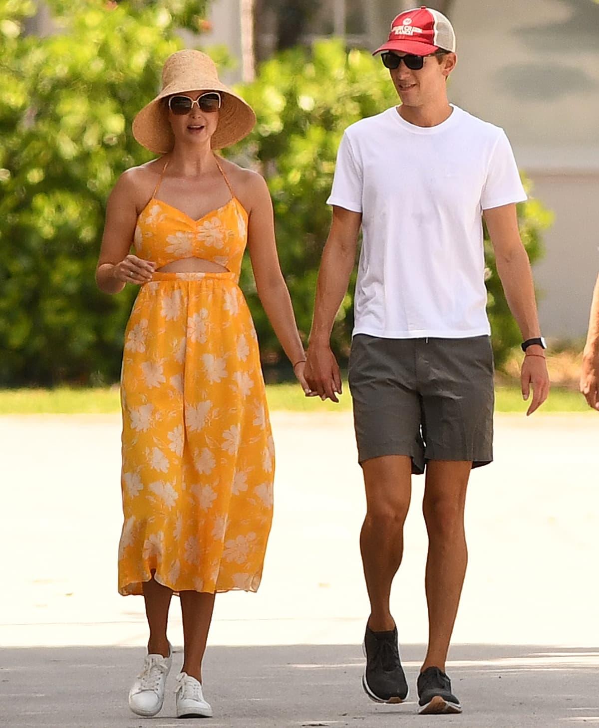 Ivanka Trump wears a yellow cutout sundress as she takes a walk with her husband Jared Kushner