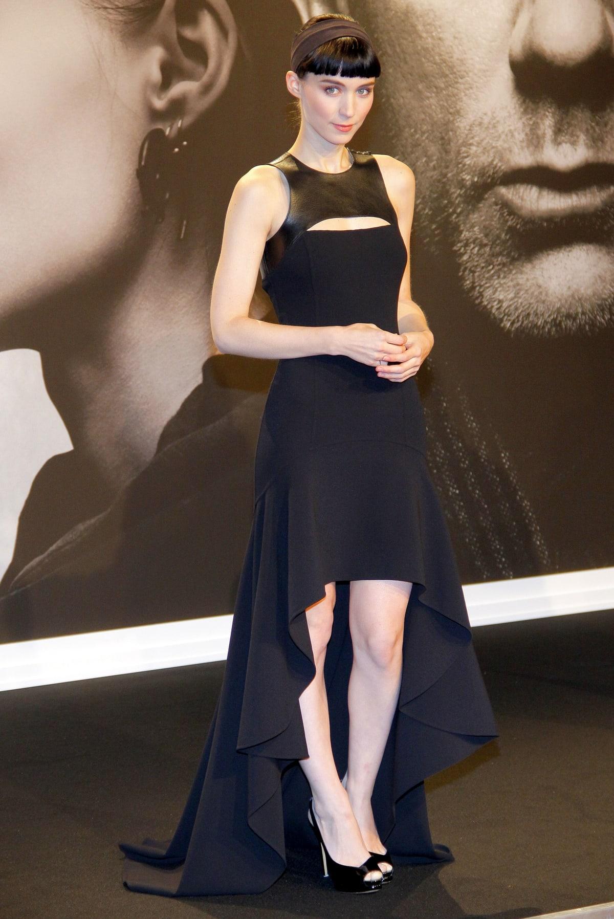 Rooney Mara wears a black a Michael Kors Pre-Fall 2012 dress with a matching headband and Nicholas Kirkwood peep-toe heels