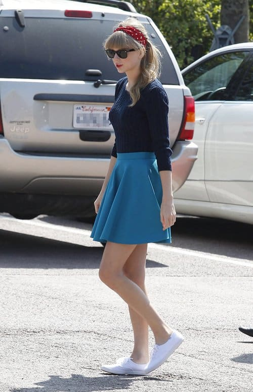Taylor Swift accessorized with white sneakers, sunnies, and a red headband