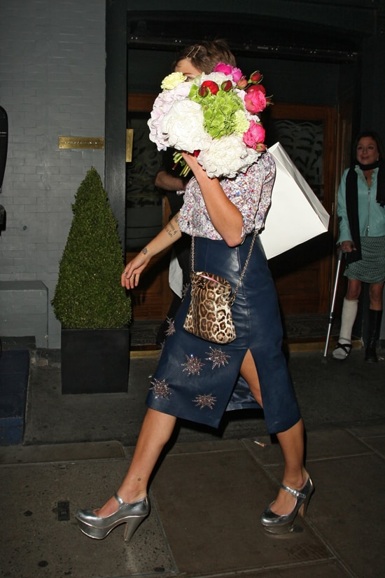 Pixie Geldof wearing a floral button down, leather skirt, leopard-print bag and silver Mary Janes