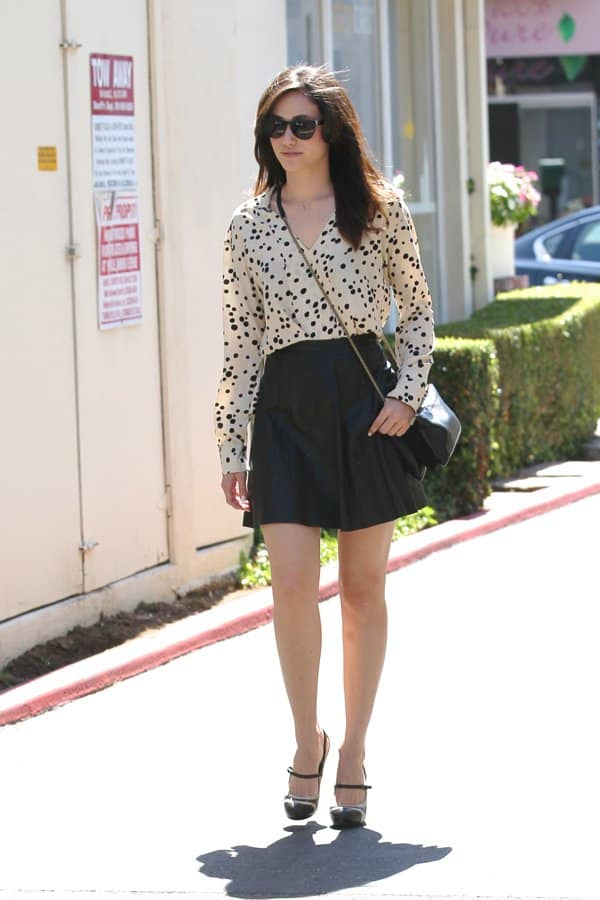 Emmy Rossum wearing a black skater leather skirt that looks charming with her dotted blouse and Mary Jane heels from Giuseppe Zanotti