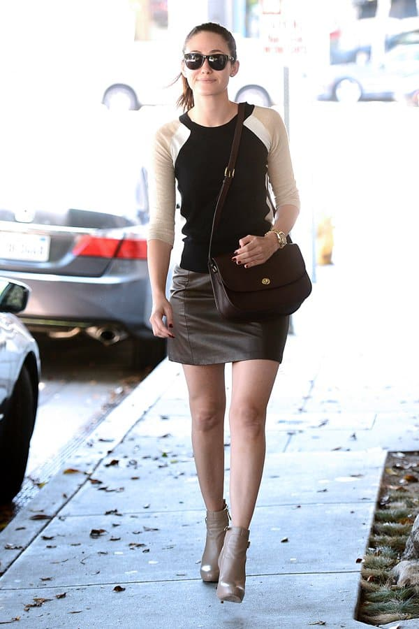 Emmy Rossum rocked a leather mini skirt with a colorblock fine-knit sweater, taupe ankle booties, a brown bag and black sunnies