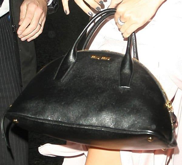 Daisy Lowe with her staple gold-trimmed black Miu Miu Bugatti tote
