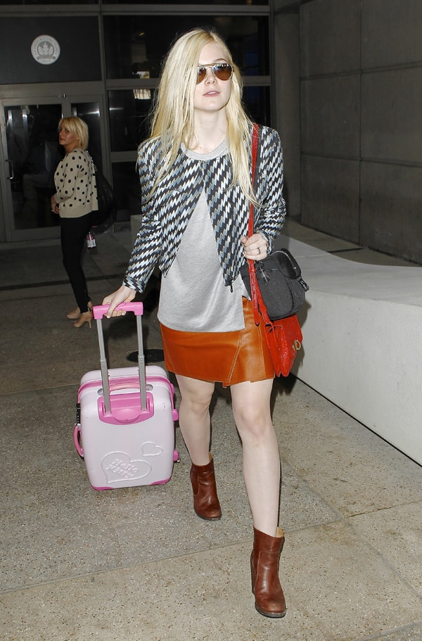 Elle Fanning in a tight brown tan leather skirt, arrives at Los Angeles International Airport (LAX) from Paris pulling her pink suitcase, Los Angeles on October 3, 2013