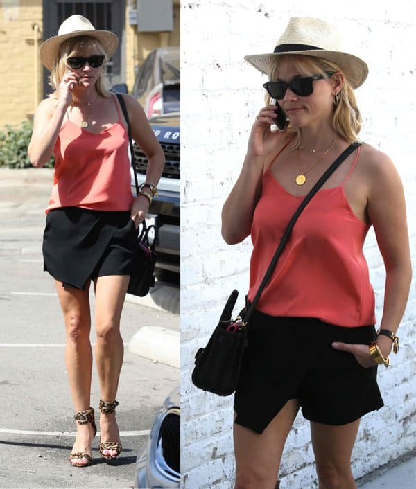 Reese Witherspoon, wearing leopard-print high heels, arrives by the back door at the Rossano Ferretti Hairspa, in a straw hat while talking on her cell phone in Los Angeles on May 1, 2014