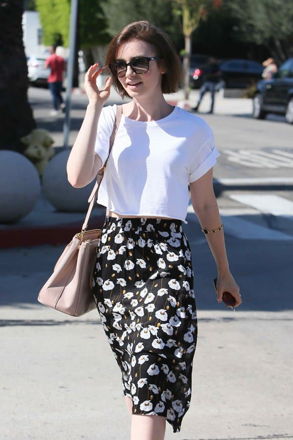 Lily styled her skirt with a boxy cropped shirt, a pair of high-heeled sandals, a nude-tone Prada 'Saffiano Lux' tote shoulder bag and a pair of sunglasses