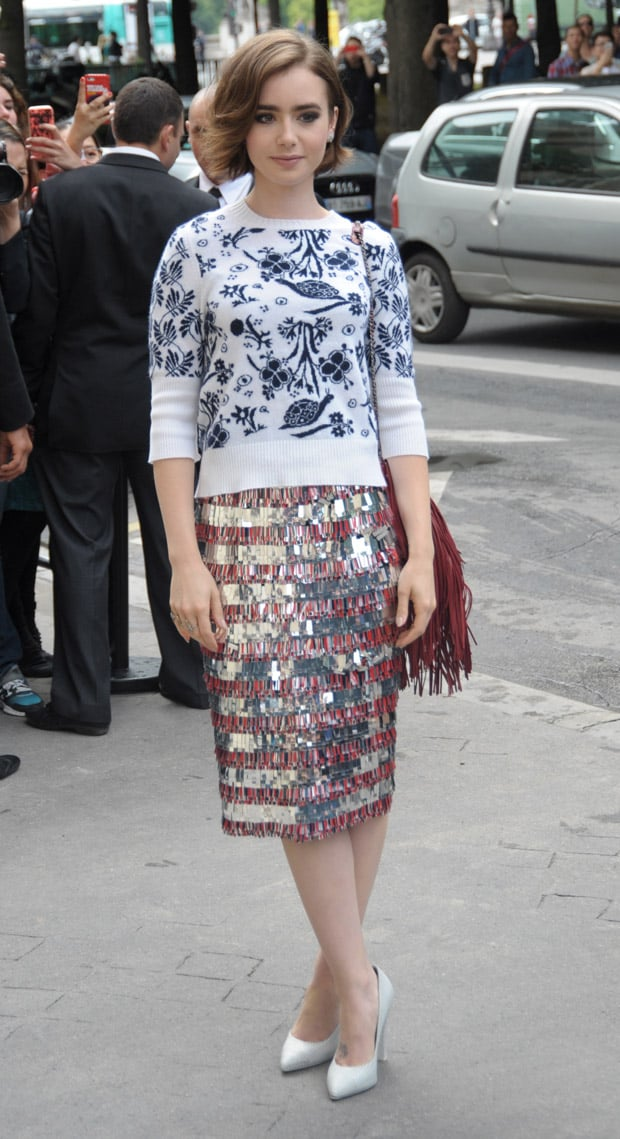 Lilly Collins wearing a metallic fringed skirt, a contrasting printed sweater, striped pumps, and a fringed bag