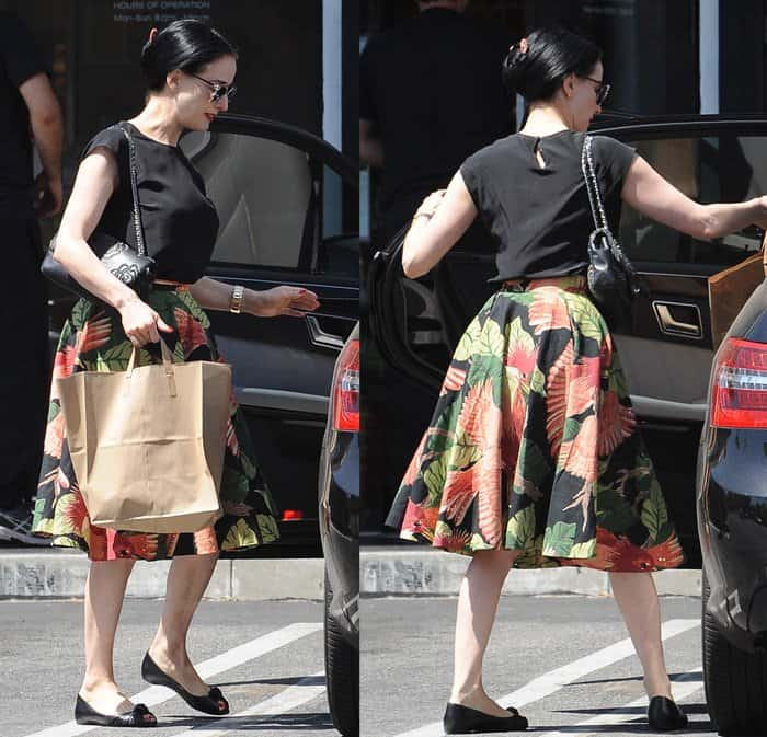 Dita Von Teese wore her printed skirt with a plain black shirt, a pair of peep-toe flats, a chain-strapped shoulder bag, a pair of sunglasses and her signature red lips